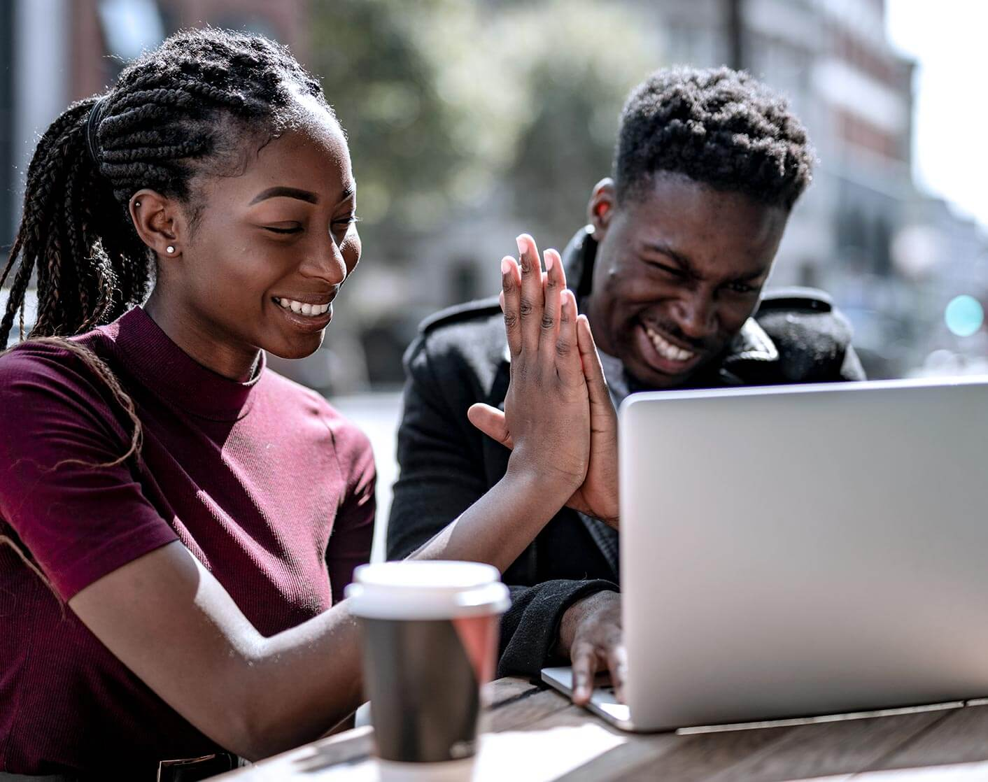 Black woman and black man high five looking at laptop
