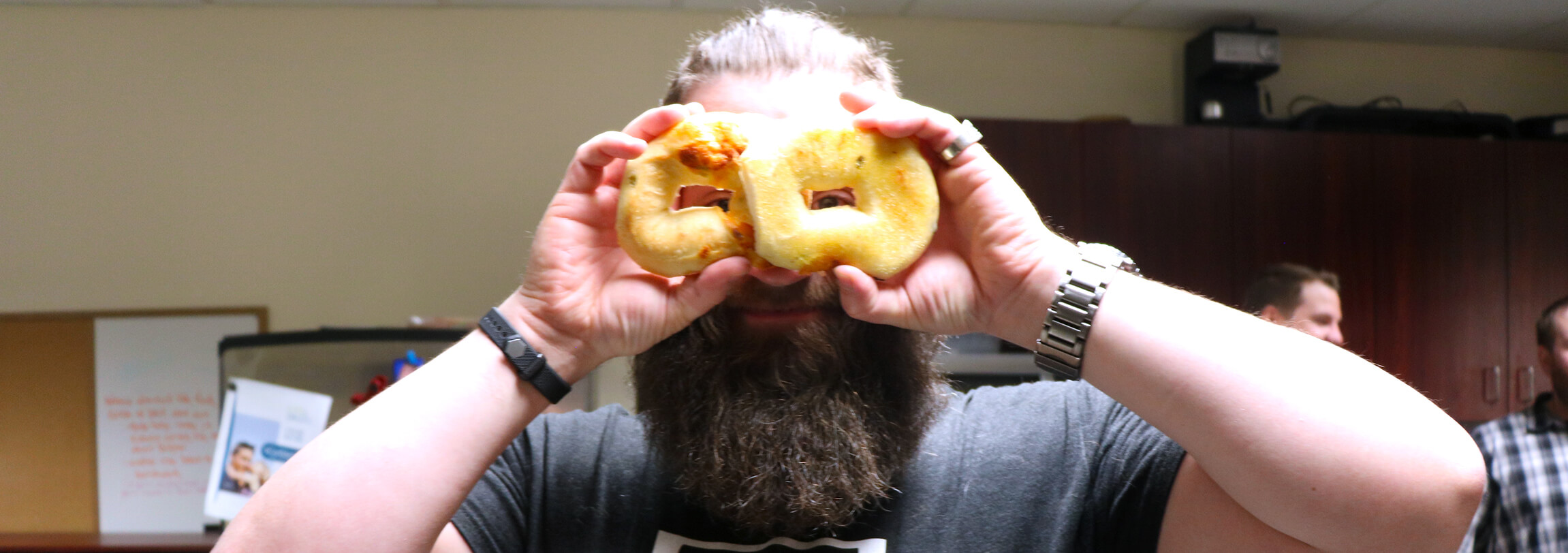 Maplewave employee holding bagels up to make pretend eye glasses