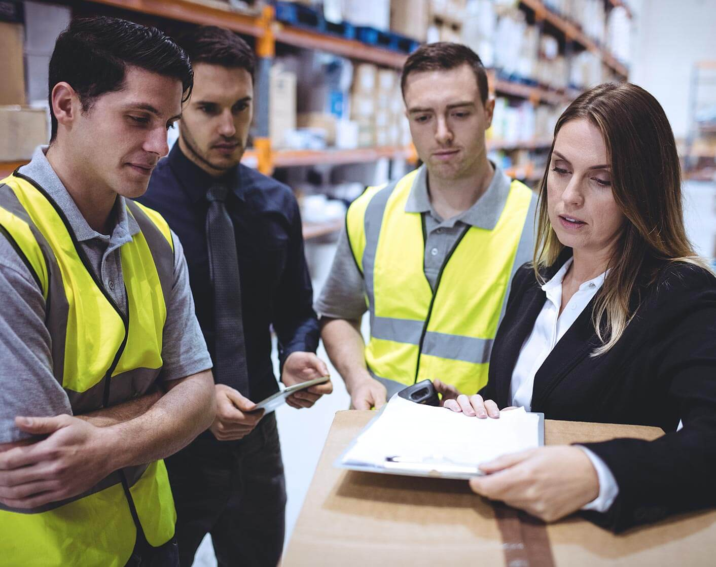 two male warehouse workers talking in a group with a business and business woman holding papers