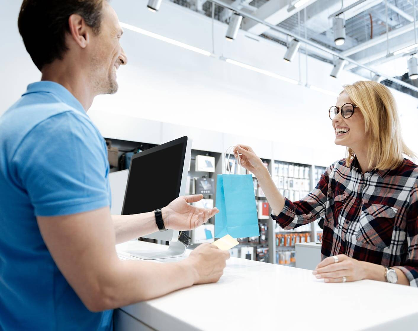 white make store clerk behind counter passing shopping bag to white female customer