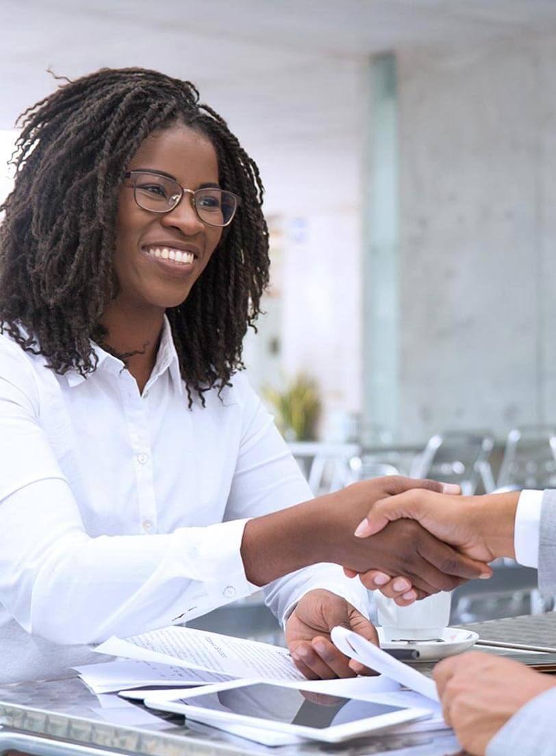 Black woman in white shirt shaking hands with another person