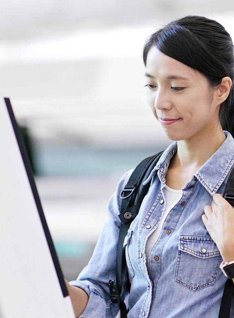 Asian woman wearing a back pack using a kiosk