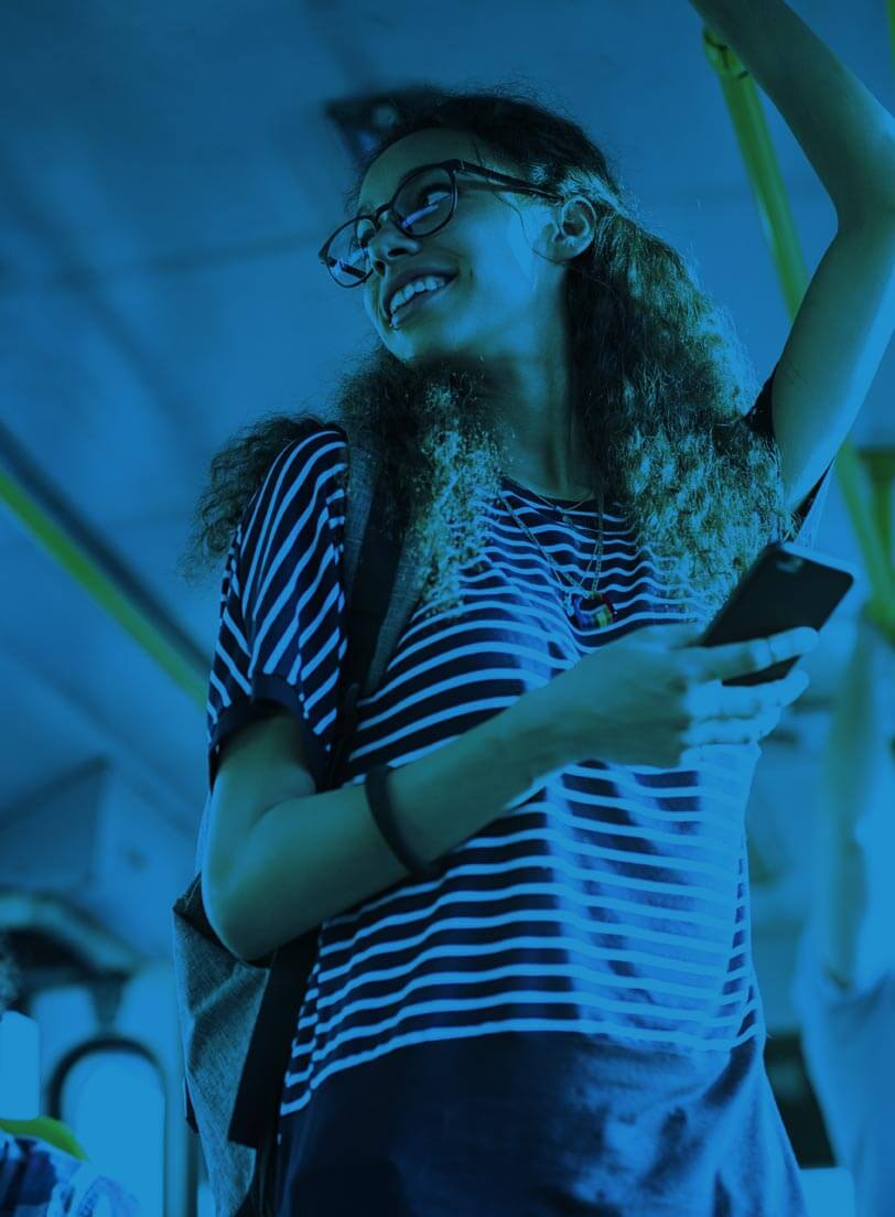 young white woman standing on bus holding mobile phone blue filter over image