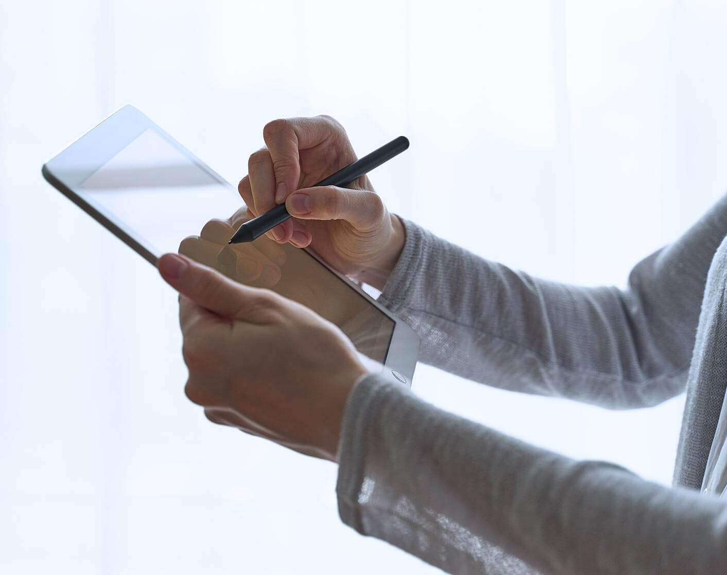 white man holding up tablet using a stylus pen on it