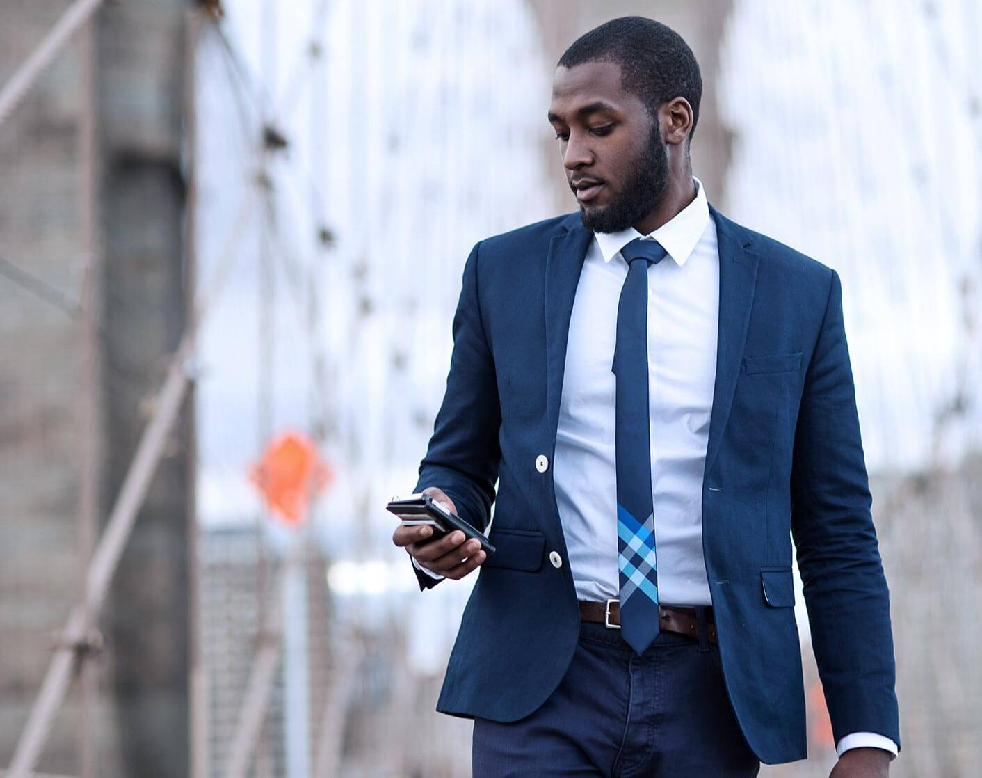 Black man in suit walking outside looking down at his mobile phone while he walks