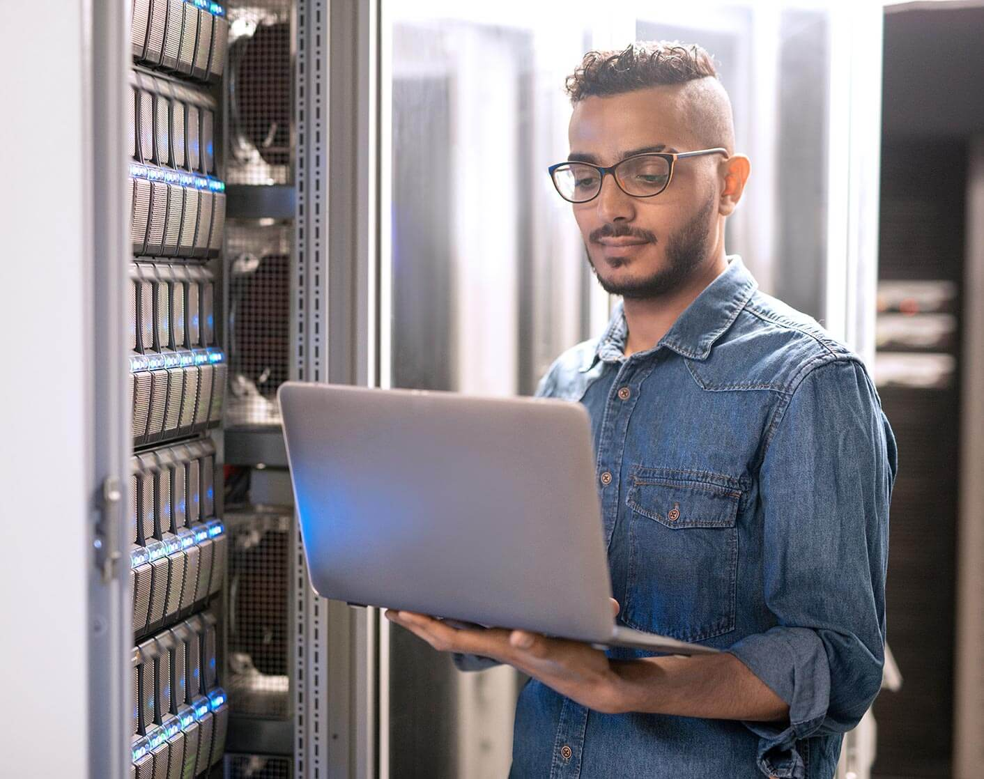 Asian man holding laptop in front of bank of computer servers