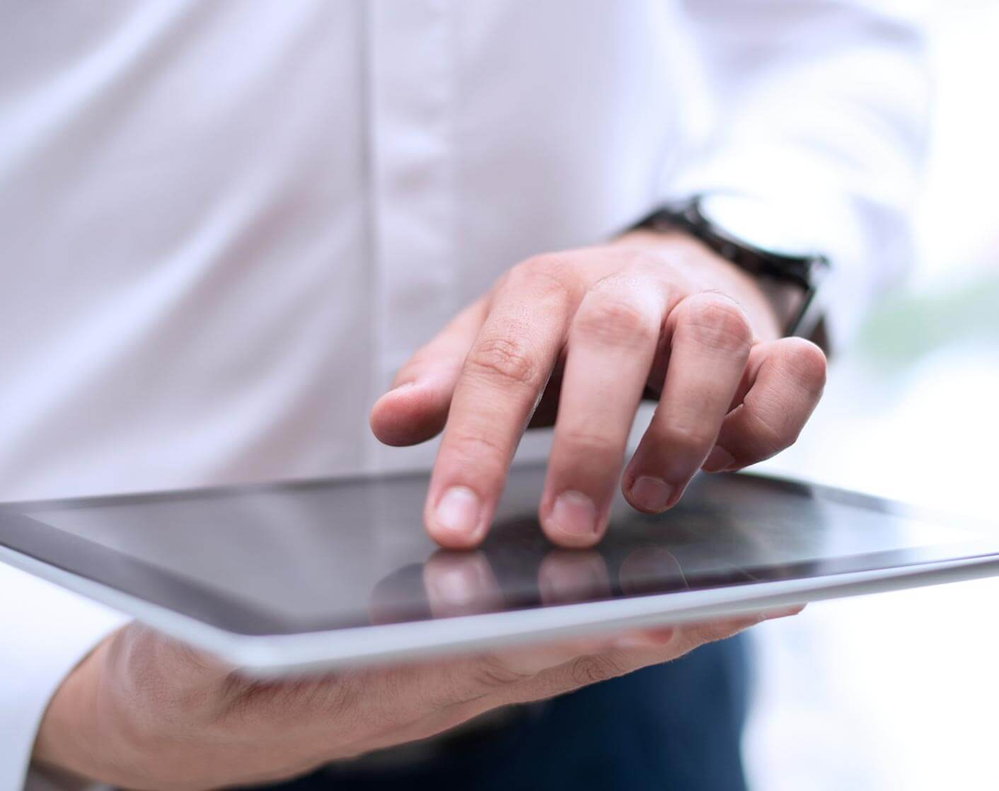 close up of white business man holding a tablet flat while using it