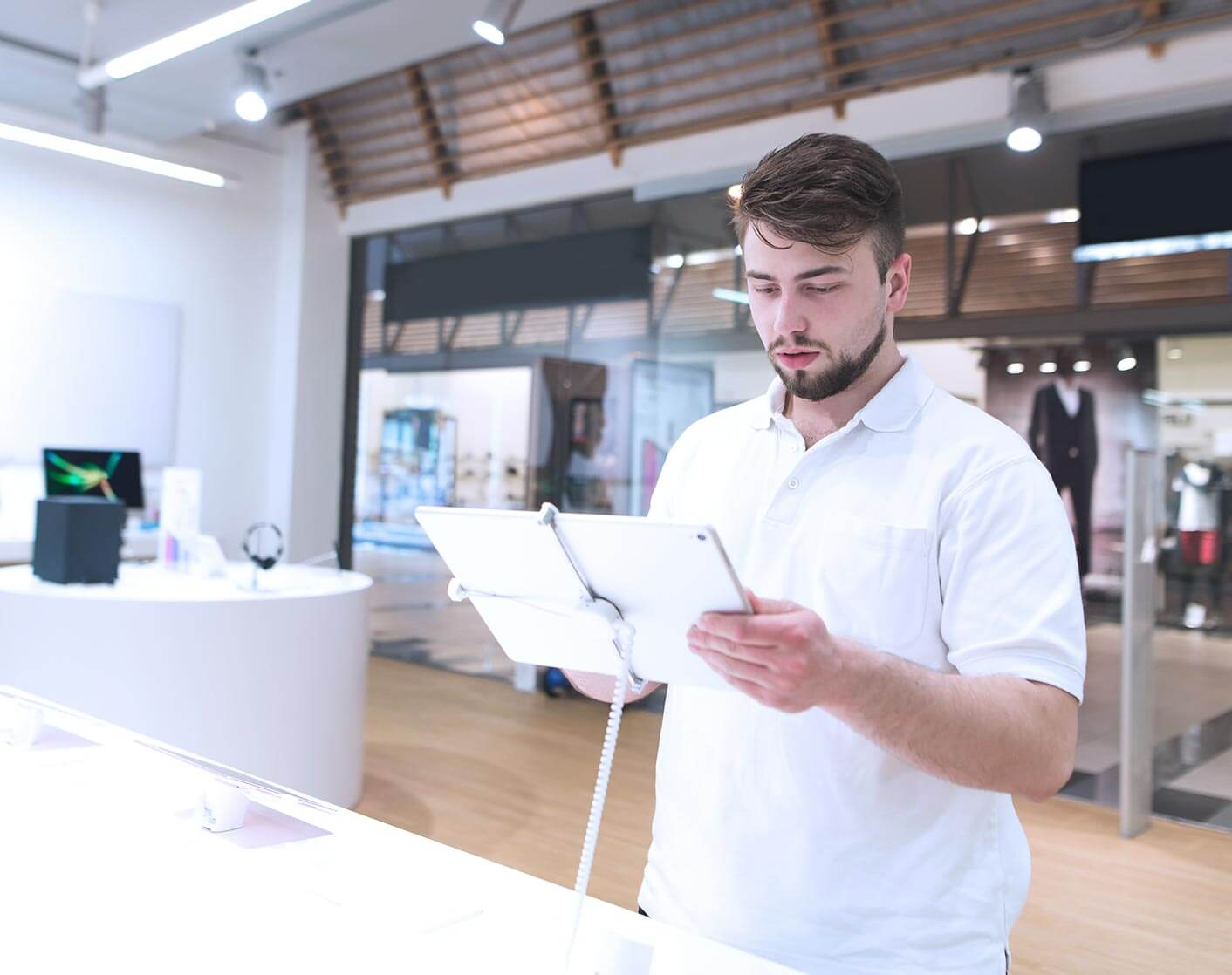 white man in white shirt looking at a display tablet in a store