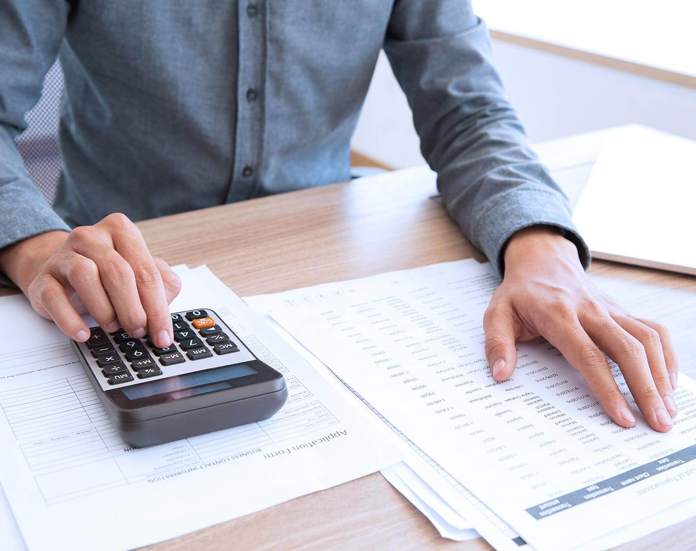close up of Asian Man in blue dress shirt looking at numbers on paper and adding them to calculator