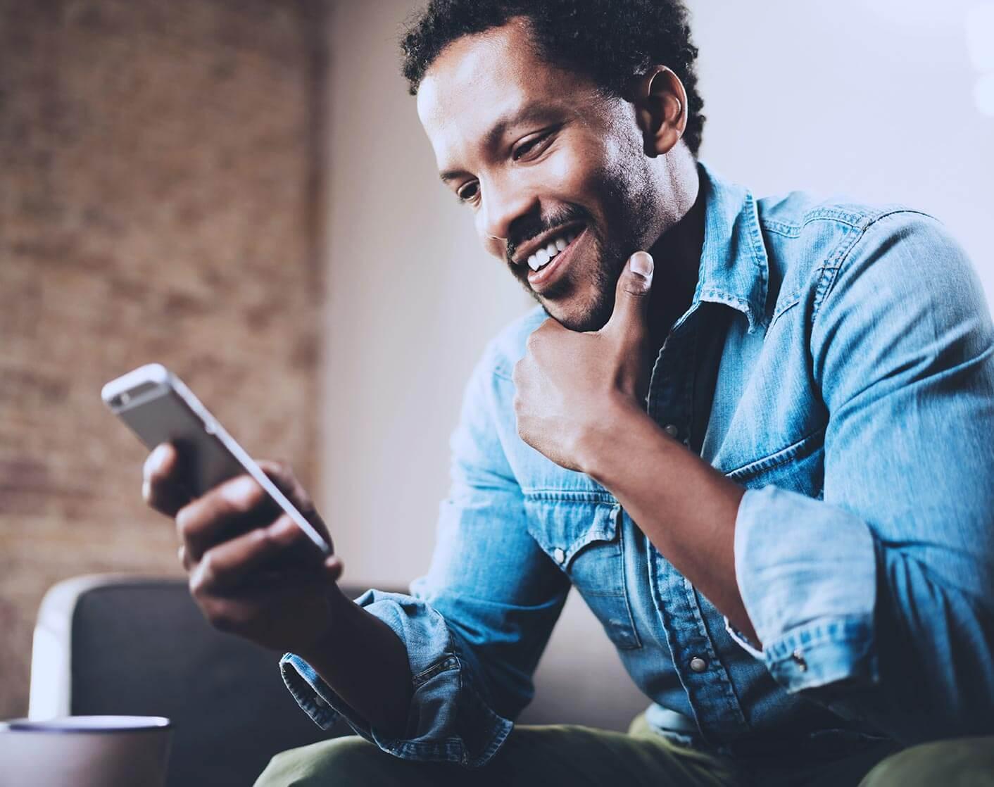 close up shot of black man sitting down wearing jean shirt looking at smart phone