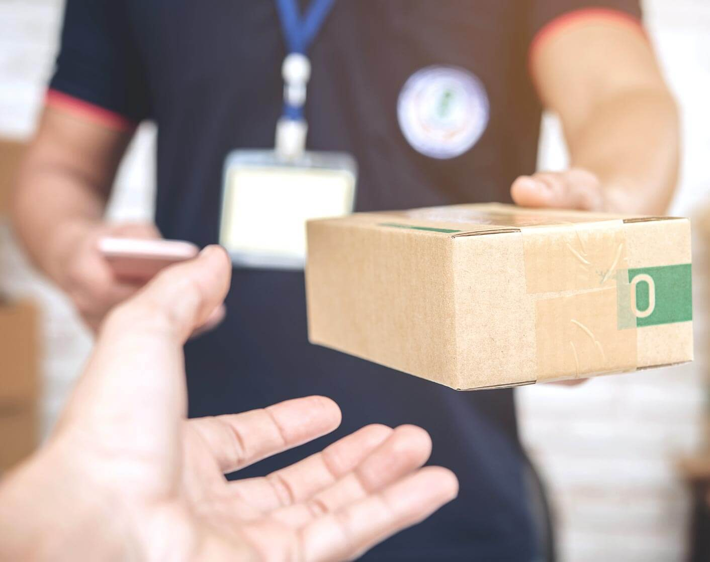 close up of a delivery person handing a small box to customers hand