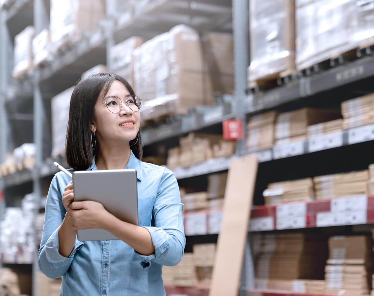 Asian woman in warehouse looking up away from camera holding a tablet and stylus
