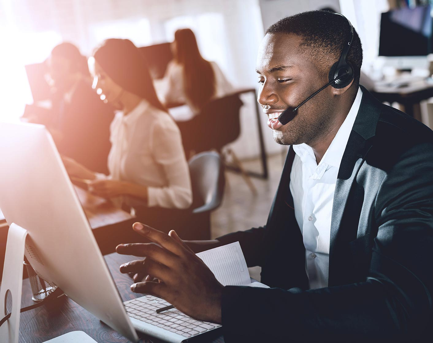 black man providing online support in a support desk office wearing a headset