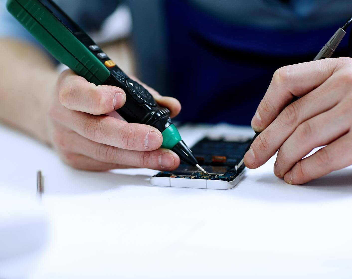 close up of a white man re soldering a mobile phone