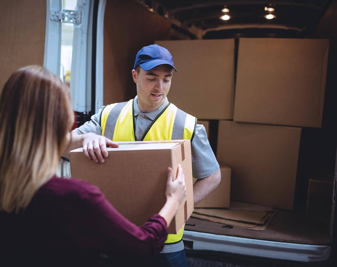 Male courier delivering package to blonde woman out of a delivery truck