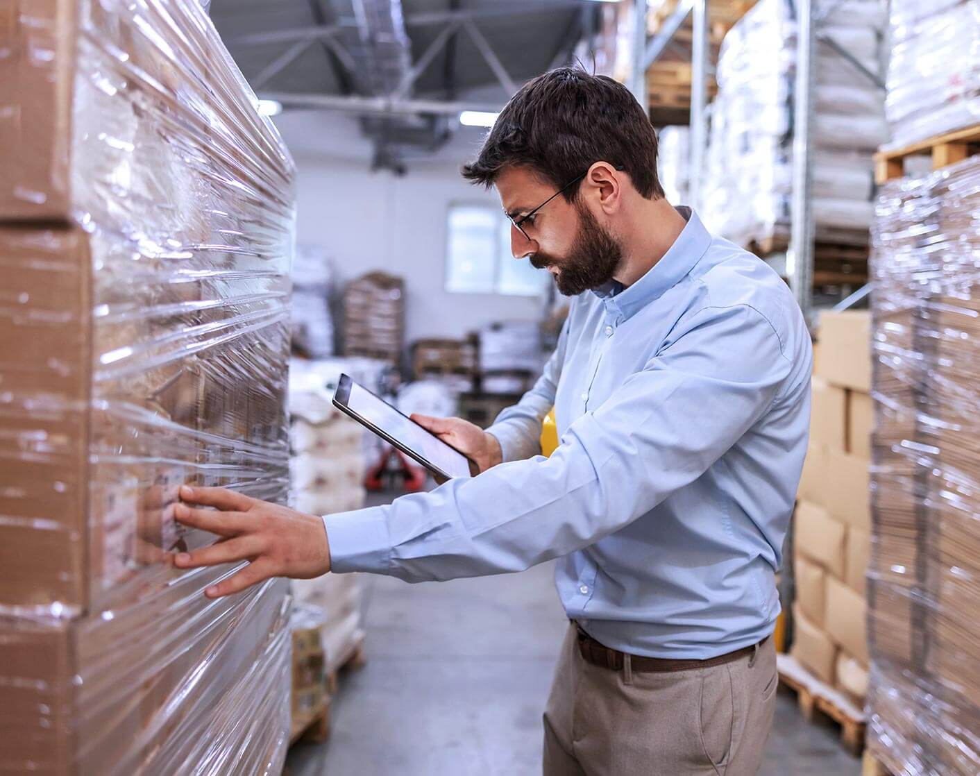 white man with beard in blue dress shirt checking pallet in warehouse using a tablet