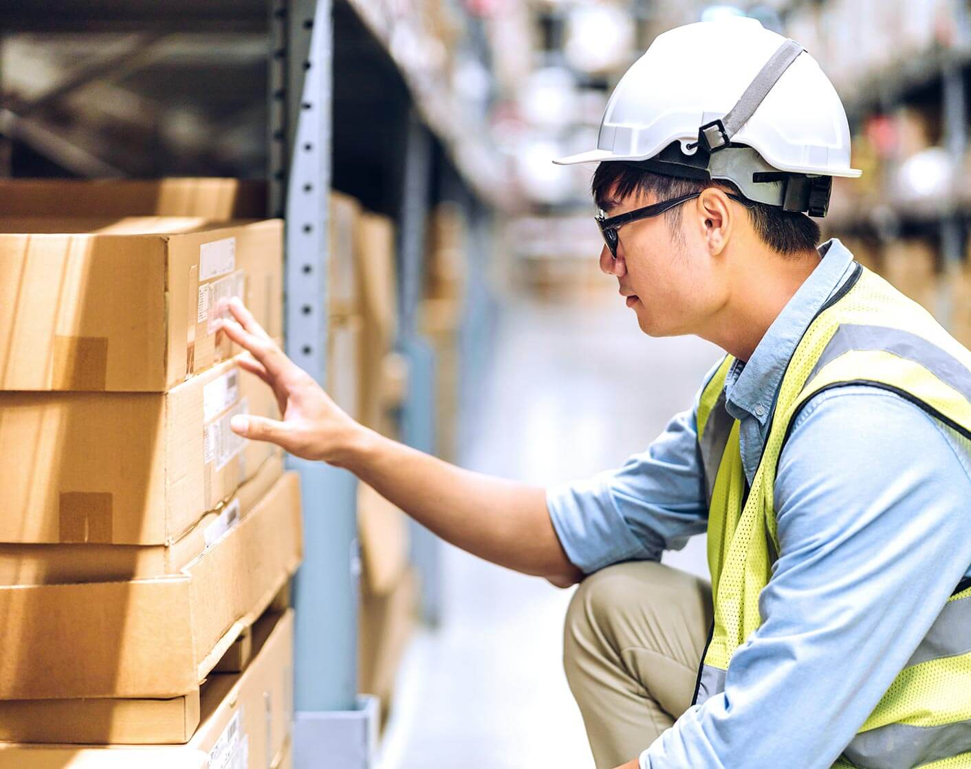 Asian man with hard hat and safety vest looking at packages on warehouse shelf