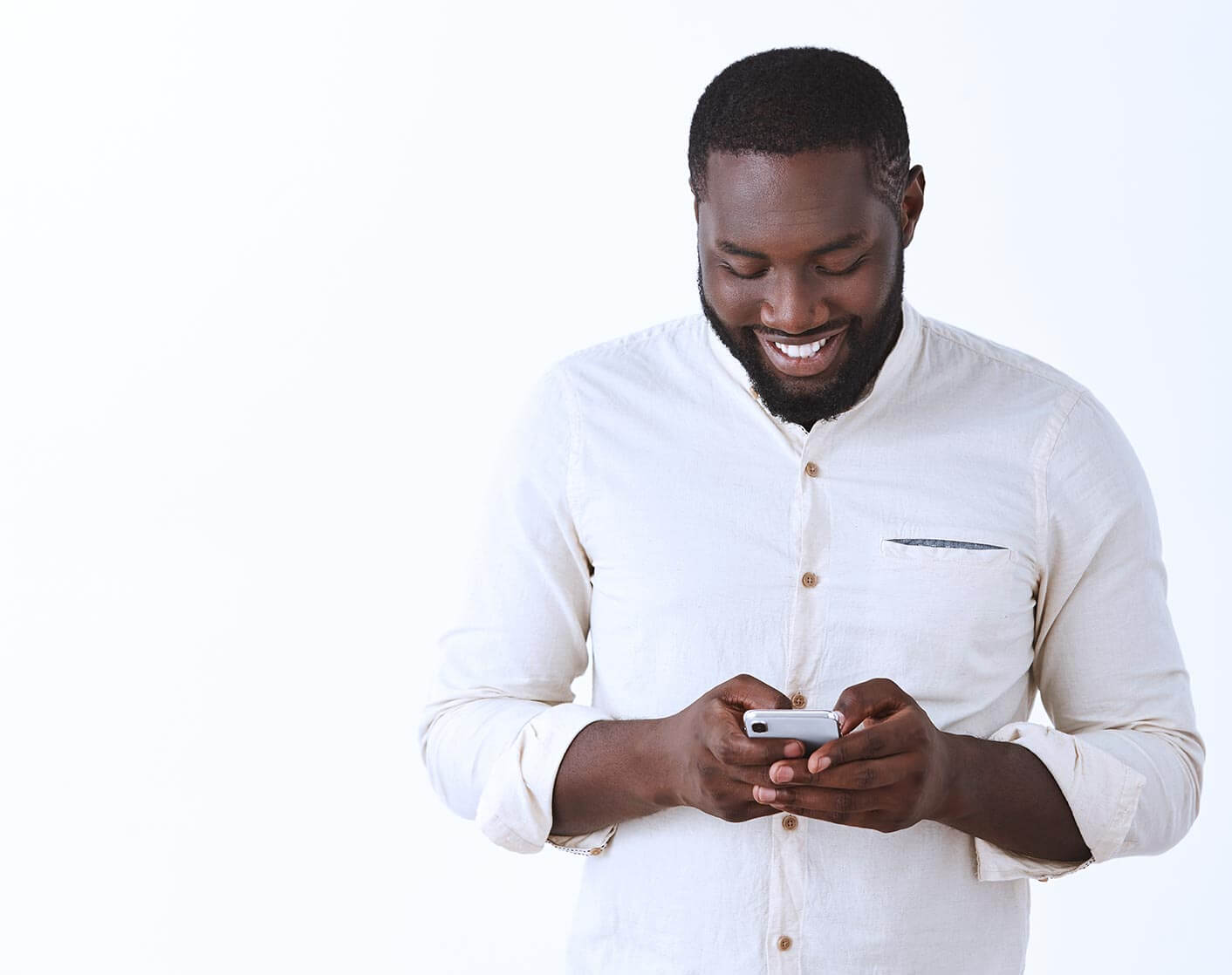black man in white shirt looking at mobile phone