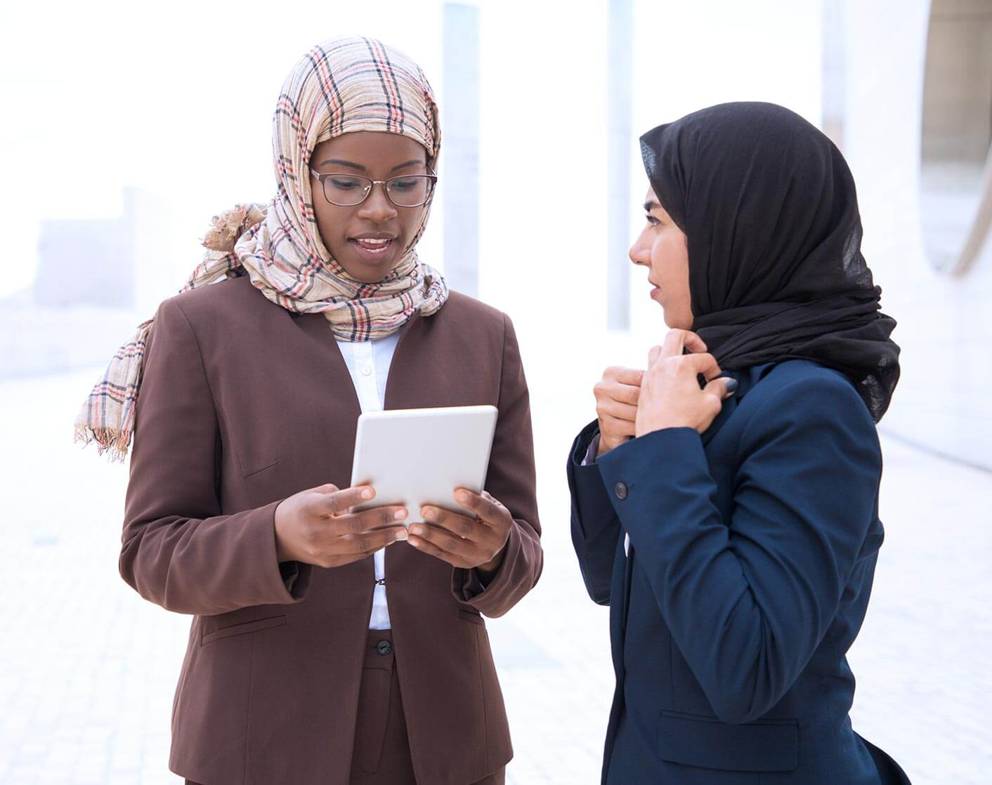 two women in head scarves talking while looking at mobile phone