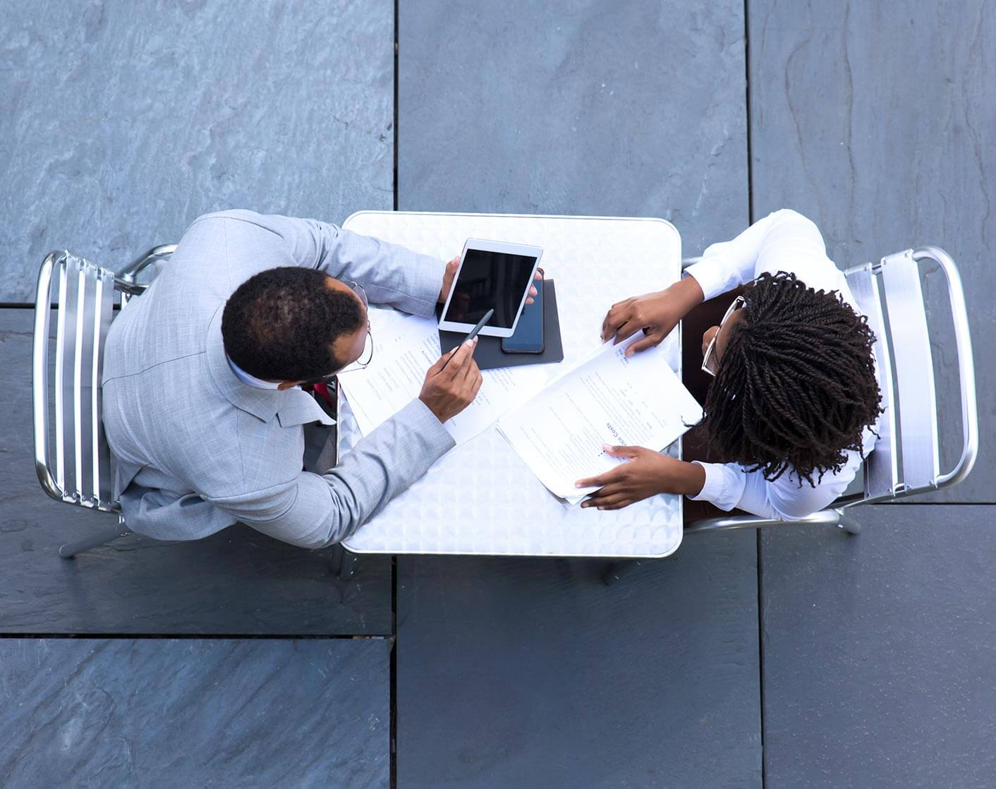 overhead shot of man and woman sitting opposite each other at a small table looking at a tablet