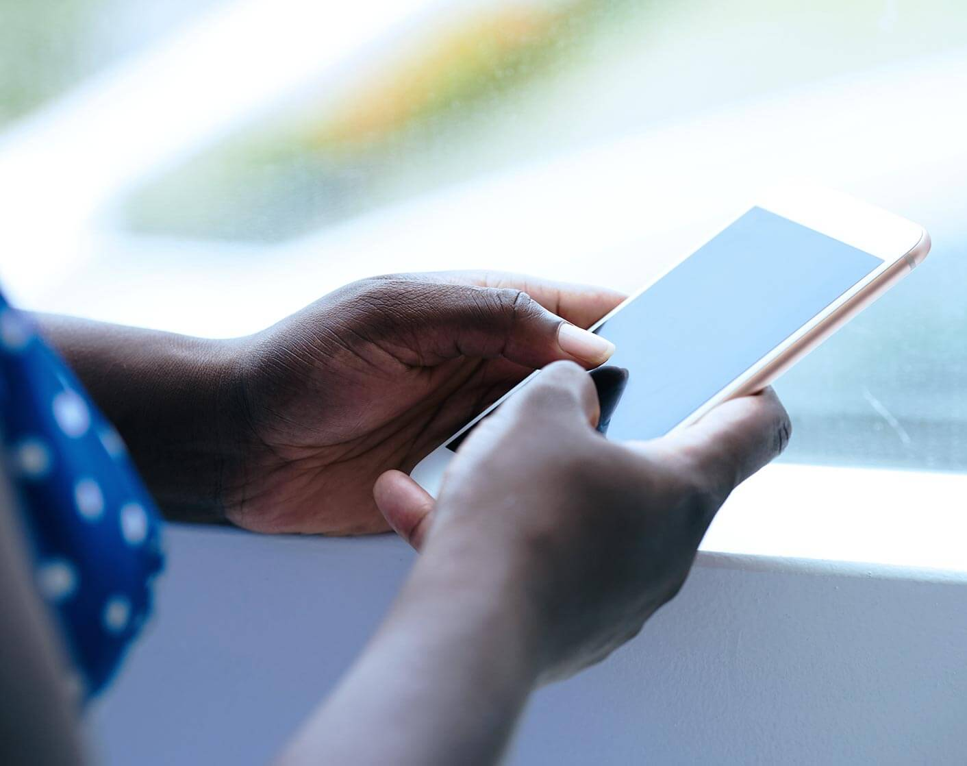 close up of a black woman using a mobile phone