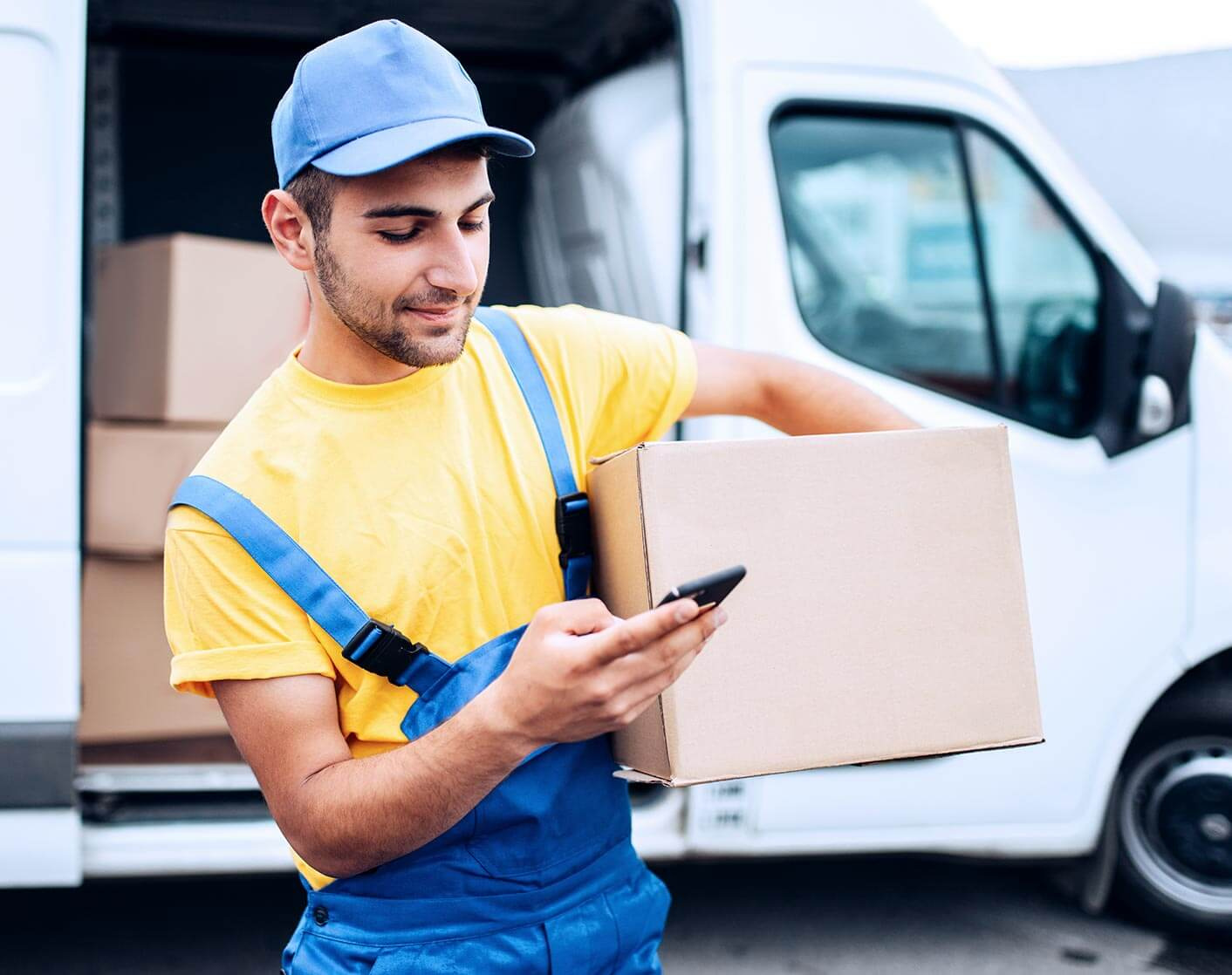 white man dressed as a courier delivering a package wearing a yellow shirt and blue overalls