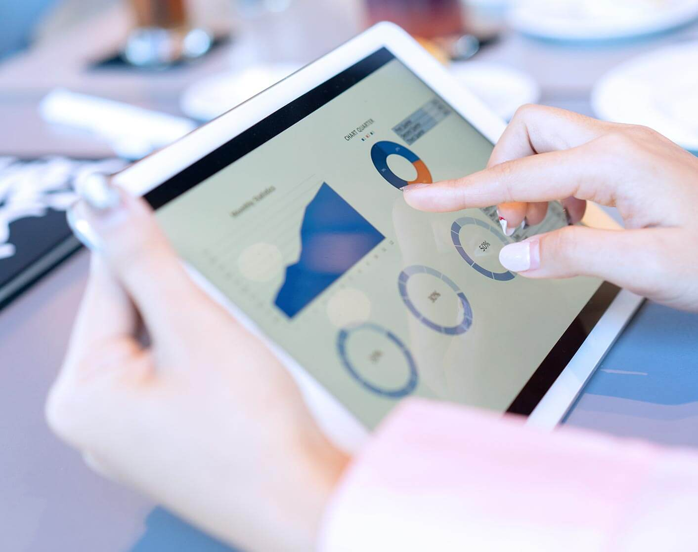 white woman using a tablet to look at data dashboard