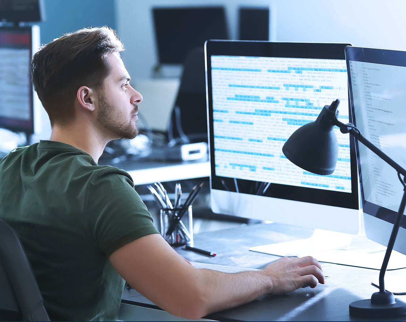 young white male programmer looking at software code on screen