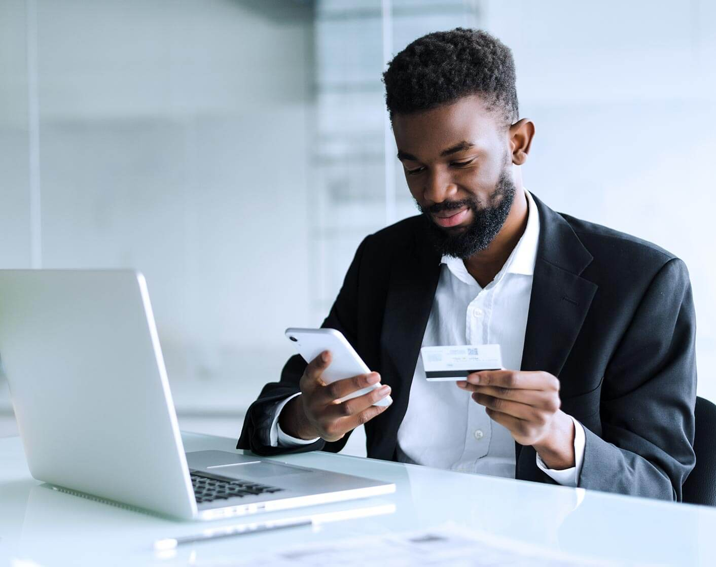 black man in suit jacket in front of laptop looking at phone holding credit card