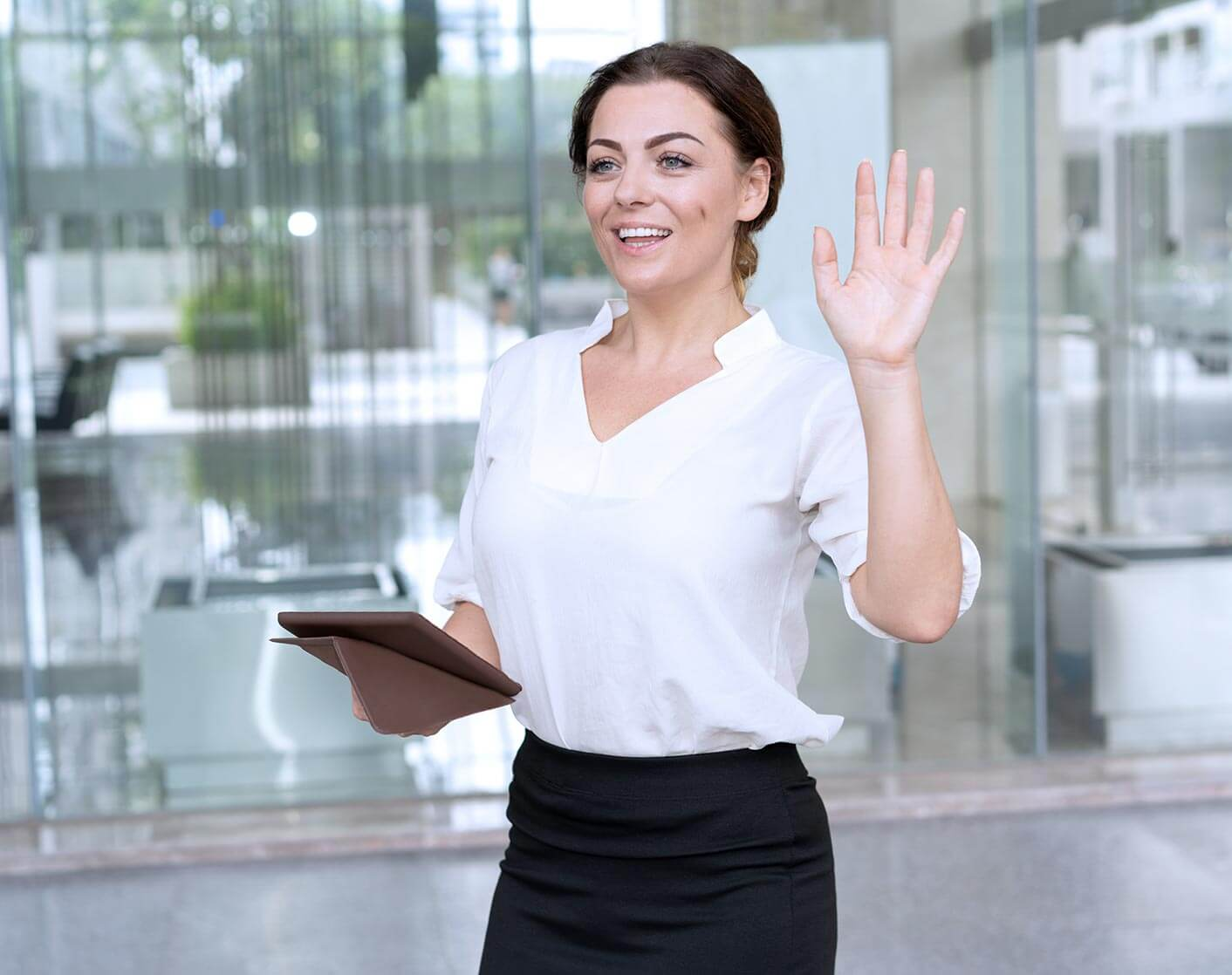 white woman outside store holding a tablet and waving to someone not seen