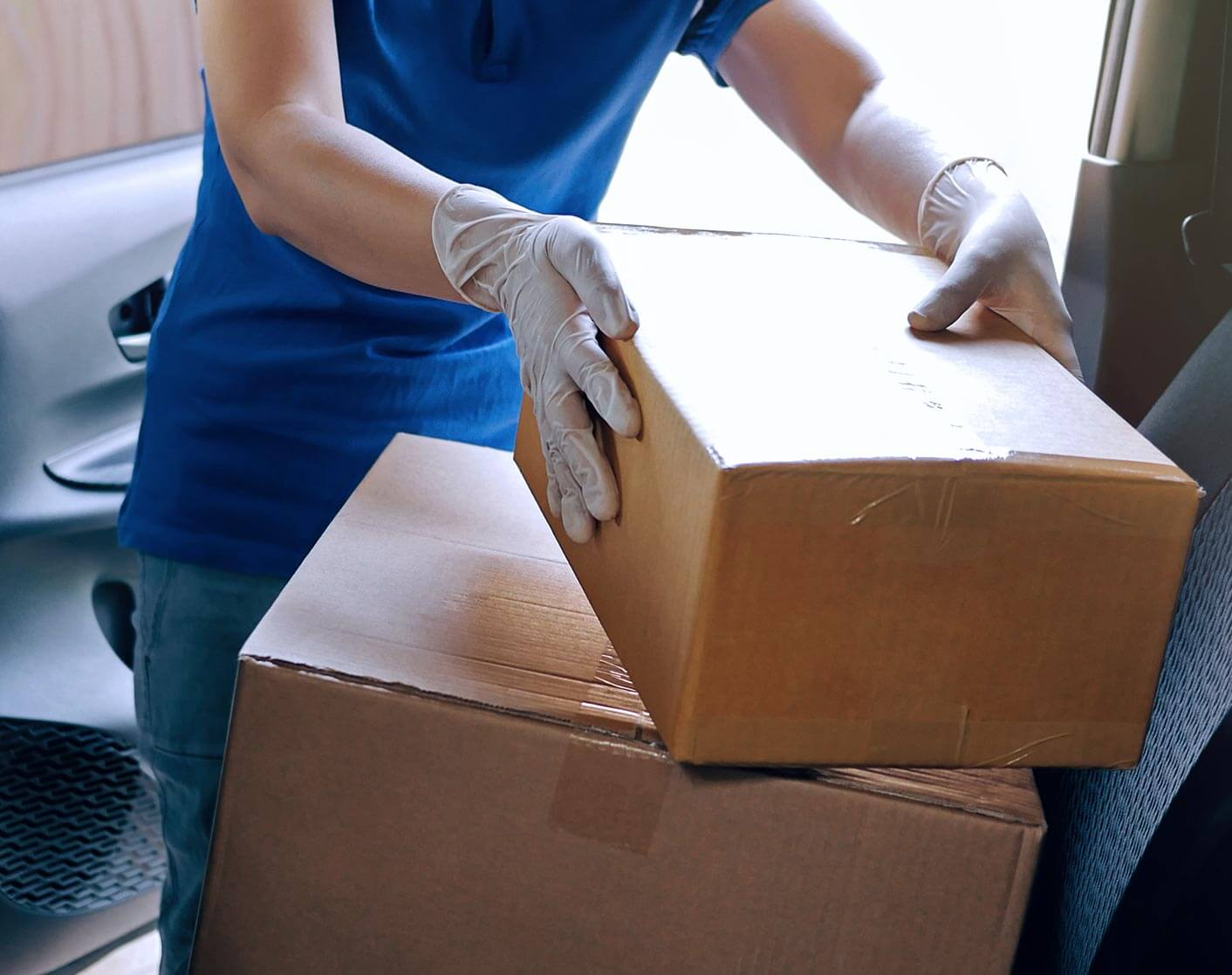 Close up of a make courier wearing gloves delivering packages