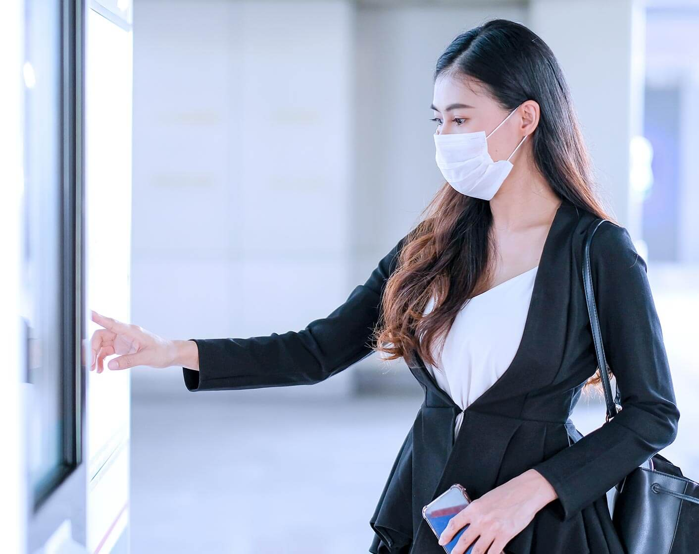 Woman with protective face mask using a kiosk in a store