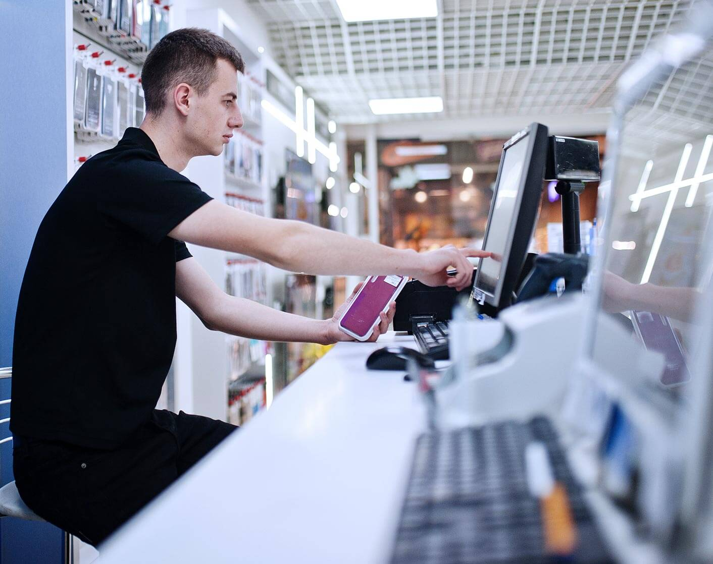 male store clerk behind store counter looking at computer screen