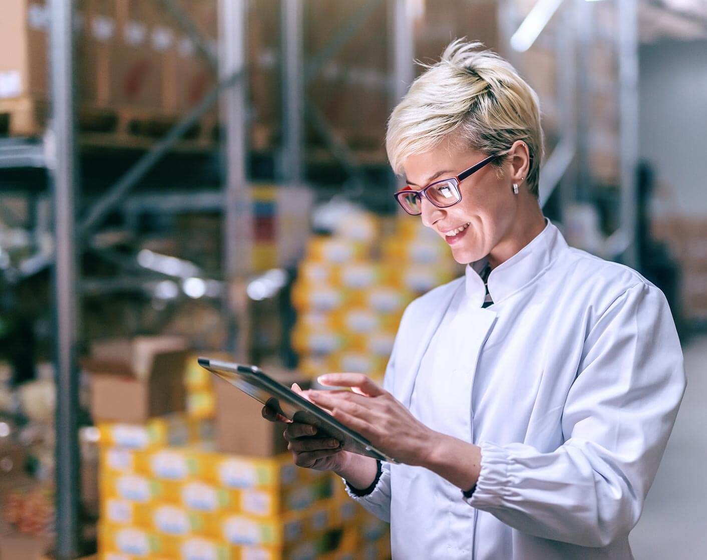 blonde woman with short hair in a warehouse looking at a tablet