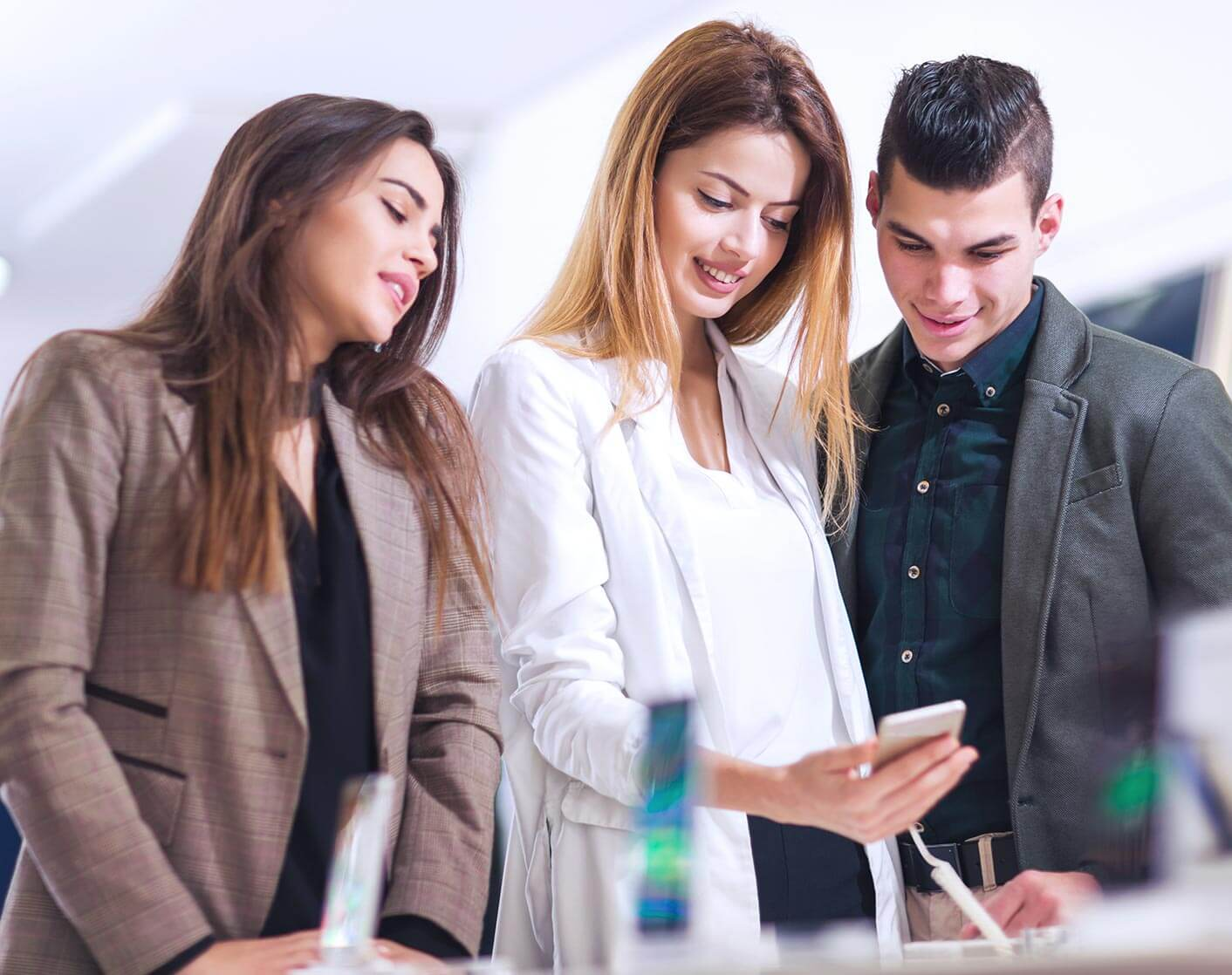 two white women and a white man in a mobile phone store looking at a display phone