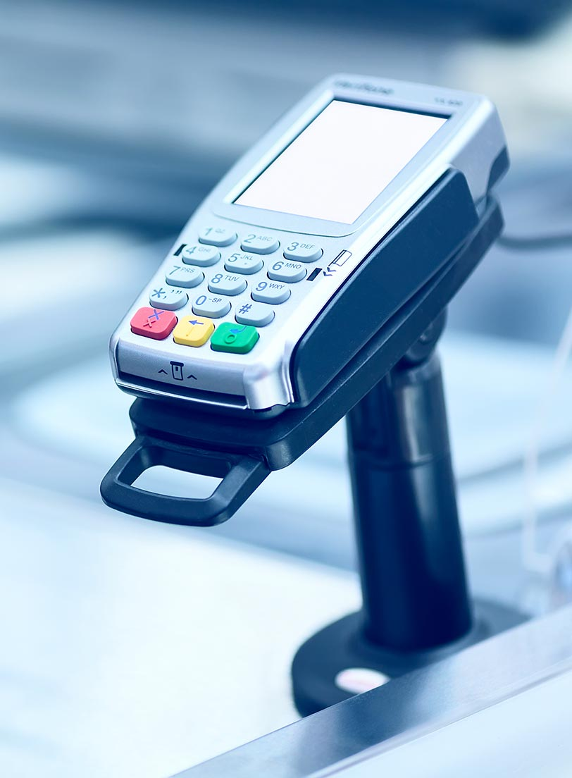 Close up of a debit credit pin pad machine on a stand on a sales counter