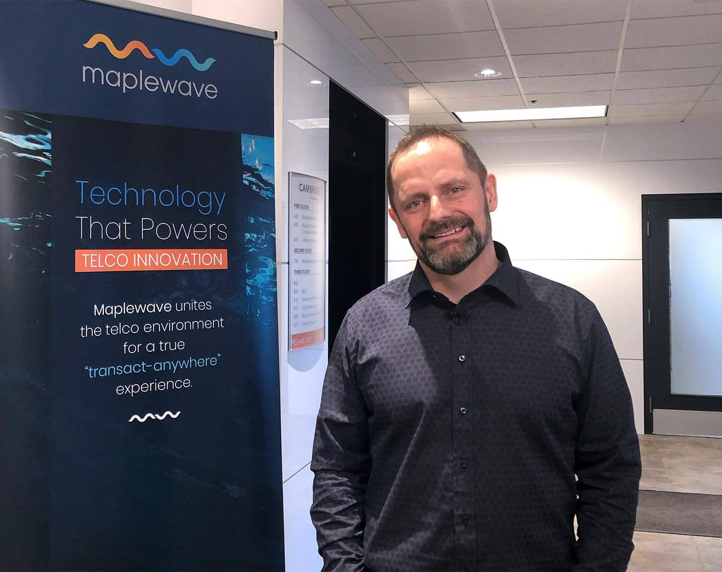 CEO of Maplewave Adam Baggs smiling to the camera in front of a Maplewave sign