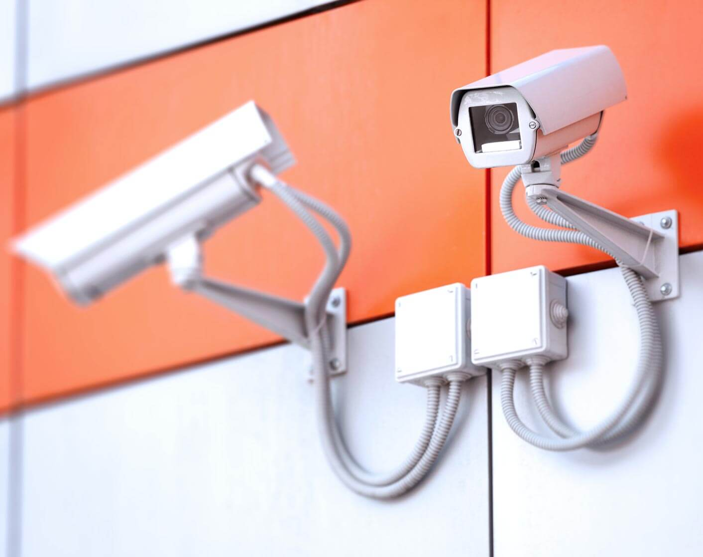 Two security cameras looking opposite directions on a white wall with an orange stripe