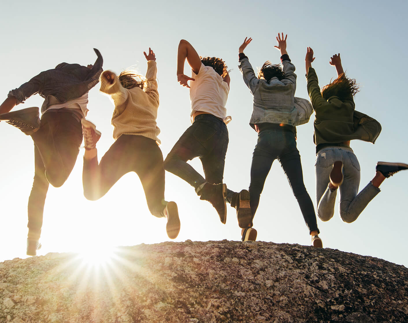 image of a group of young adults jumping on top of a crest of a hill with the setting sun in the background