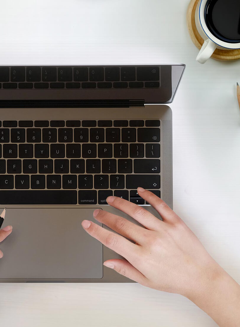 Overview of a left hand on a laptop keyboard and a cup of coffee near by