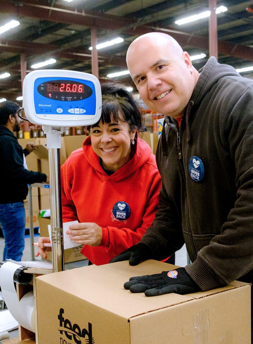Man and woman posing for a picture while packing food at a food bank