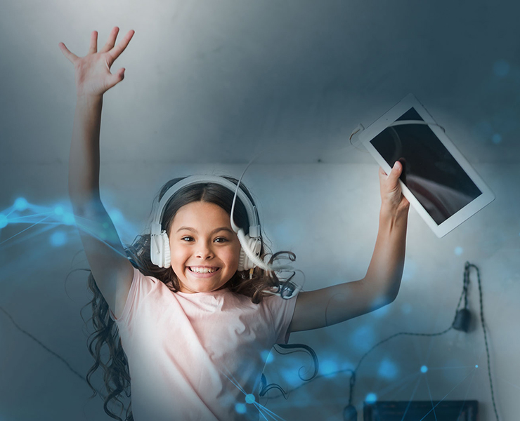 Image of a young girl with heads phones up jumping up holding a tablet