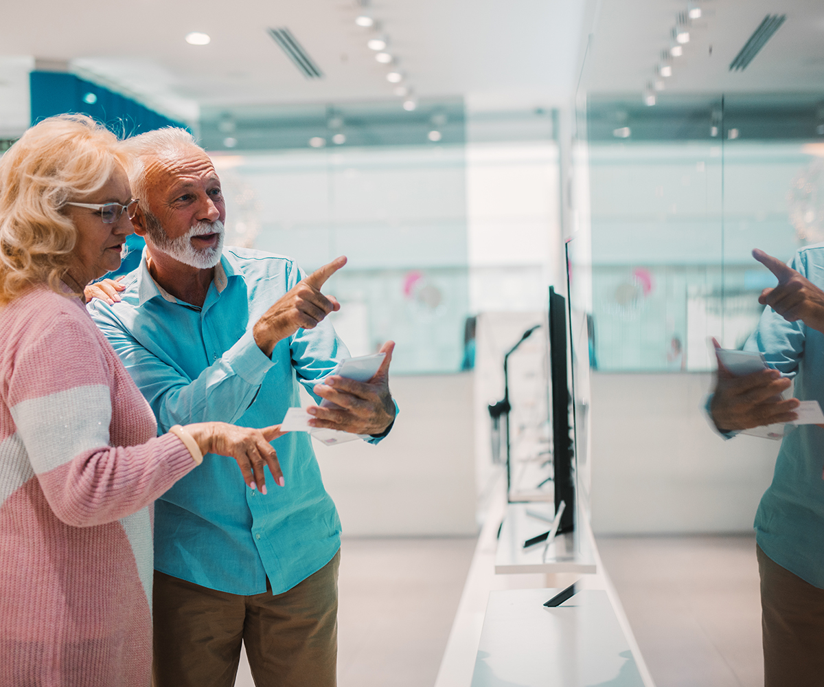 Two people looking and pointing at a TV in a retail store.