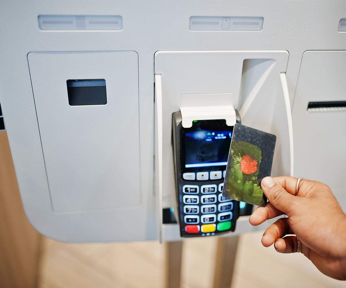 Someone paying at a kiosk with a credit card.
