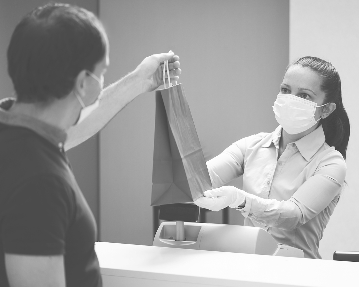 Female store clerk wearing a surgical mask passing a paper shopping bag to a male wearing surgical mask