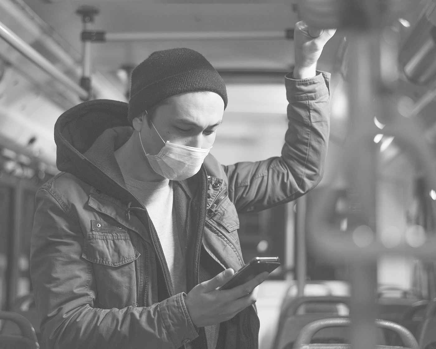 man on a bus alone holding top rail with his left hand reading his phone in his right hand, he is wearing a surgical mask