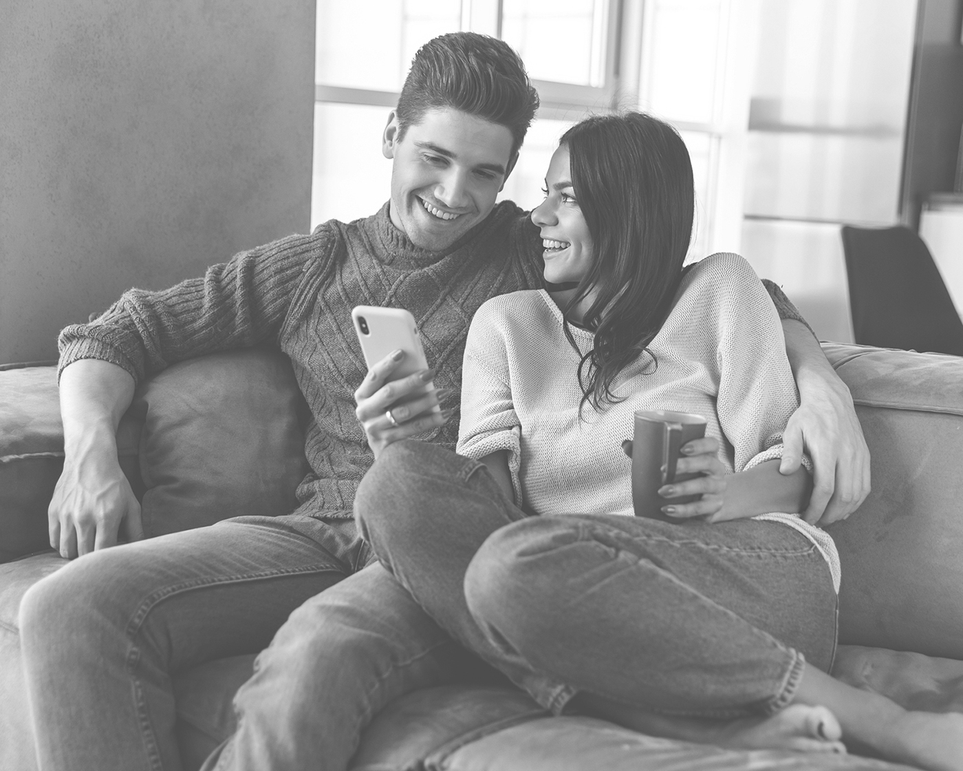 a man in cable knit sweater with his arm around a woman in a light sweater both looking at the phone in her right hand