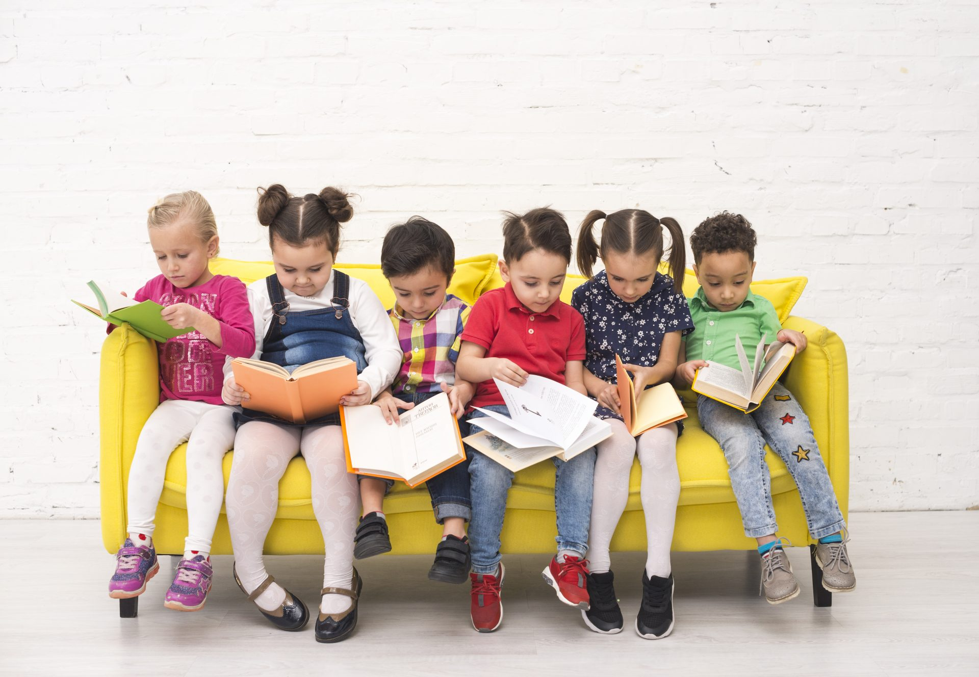 Image of 6 children sitting on a yellow couch all reading books