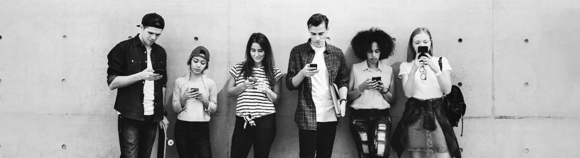 Black and white image of six young adults leaning on a wall all looking at their phones