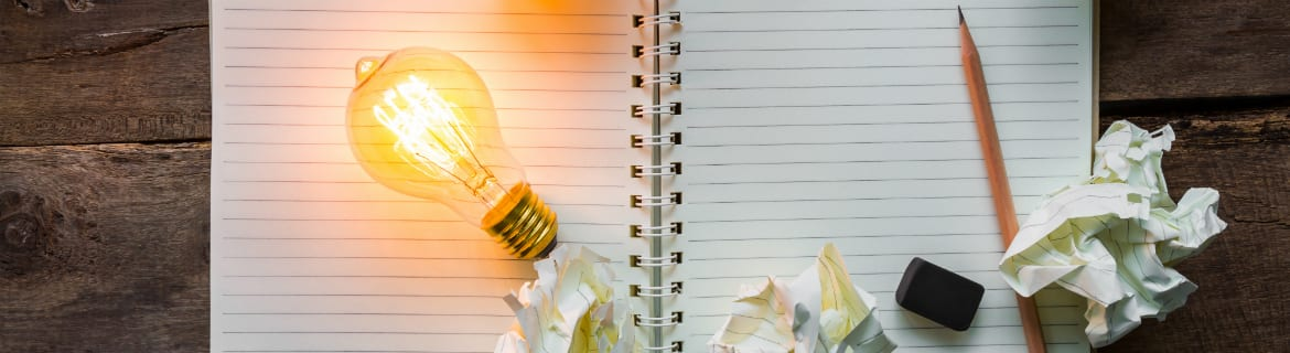 Light bulb illuminated on a blank notebook with pencil and crumpled pieces of paper